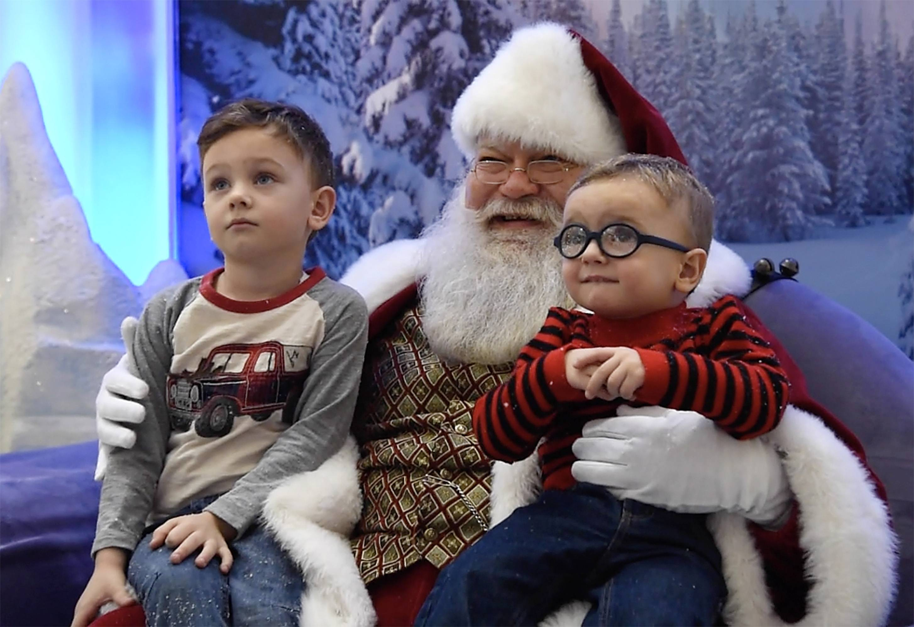 Lucas Basa, 4½, of Arlington Heights and his brother Julian, 2, concentrate on the camera while they sit on Santa's lap at Woodfield Mall in Schaumburg.