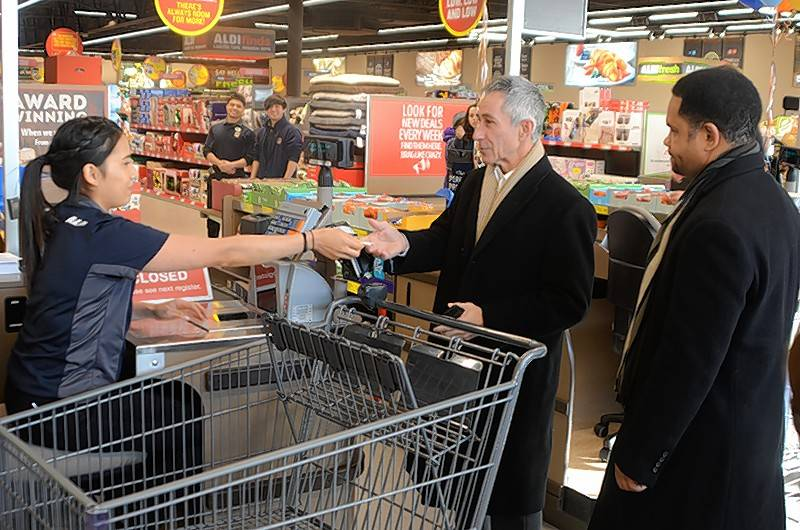 Aurora Fifth Ward Alderman Carl Franco, center, and Aurora Mayor Richard Irvin led shoppers checking out at the grand opening of a new Aldi store at 2275 W. Galena Blvd. in Aurora. (Al Benson Photo)
