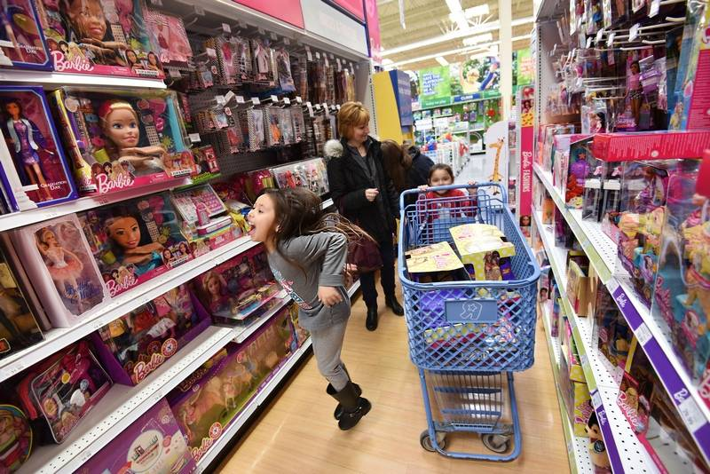 Aliyah Bresette, 7, bounces with joy as she shops in the Barbie isle at the Toys R Us on Randall Road in Algonquin with her family Thursday. Her sister Destinee Wilson, 5, pushes a full cart as their mother, Alicia Wilson, and their grandmother Dianne Godsey, all of Lake in the Hills, try to control the shopping spree. They came because they heard of the plan to close all stores.