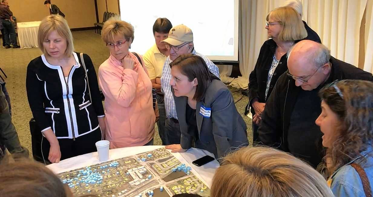 Buffalo Grove Village Planner Nicole Woods, center, talks to a crowd gathered around a table covered with a planning exercise.