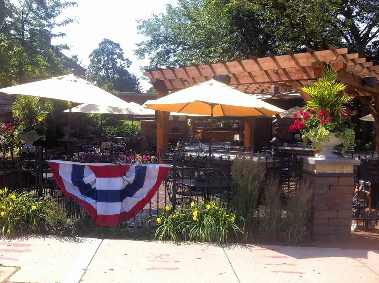 The large outdoor patio at The Office in St. Charles includes ample seating, lush plants and a wooden canopy.