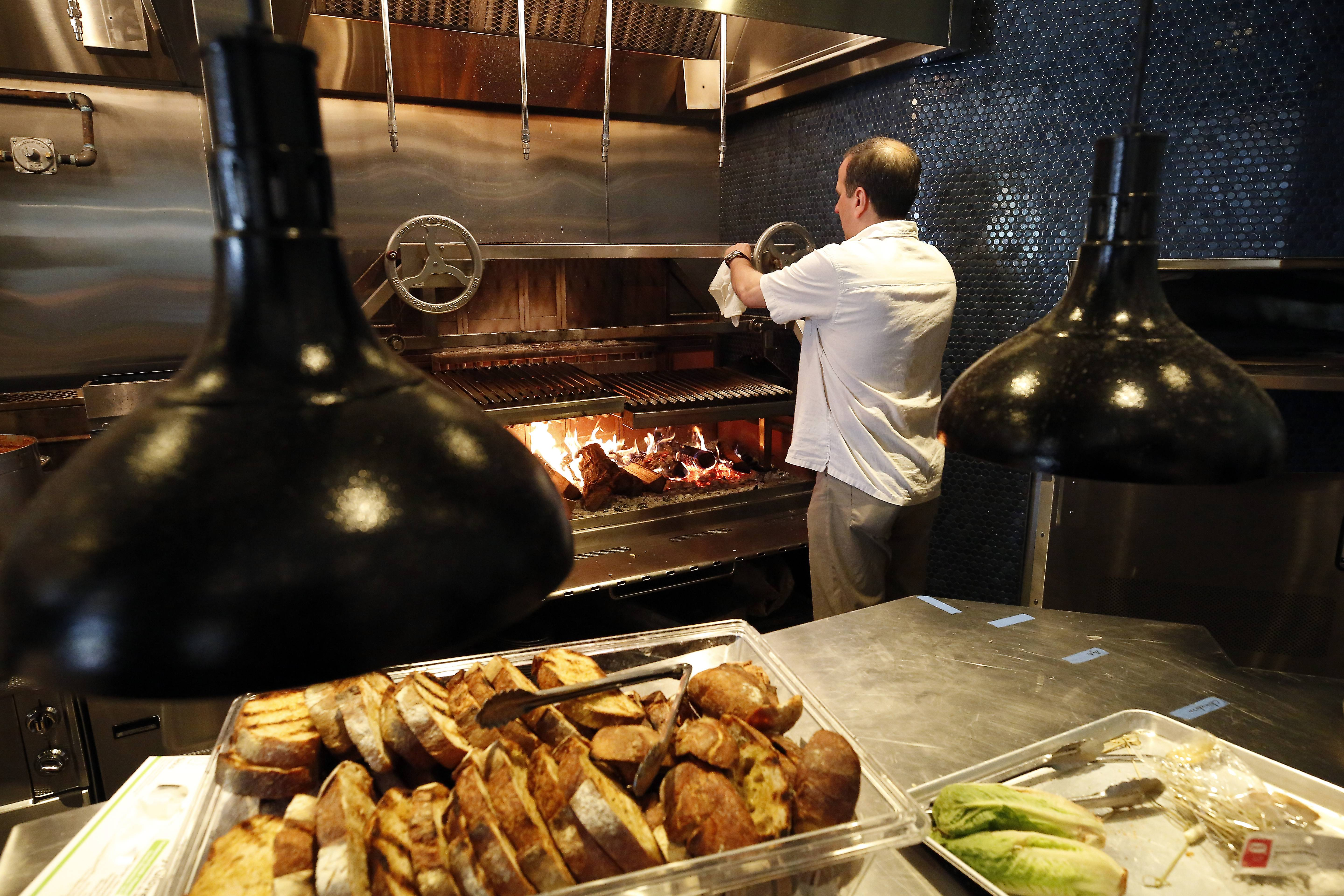 Executive chef and founder Mark Grimes works a special wood-burning grill at Che Figata, which recently opened in Naperville.