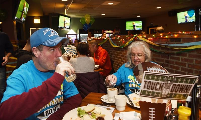 Mark Jones and his mother, Joanne Jones, both of Elk Grove Village, eat, drink and watch the game, played between Florida International University and the University of Toledo during the Makers Wanted Bahamas Bowl viewing party Friday at Real Time Sports.