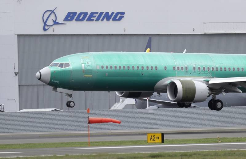 A Boeing 737 MAX 8 airplane being built for India-based Jet Airways lands following a test flight at Boeing Field in Seattle. The Chicago-based company is pulling its 2019 forecast over 737 Max uncertainty and says it's suspending its stock buybacks.