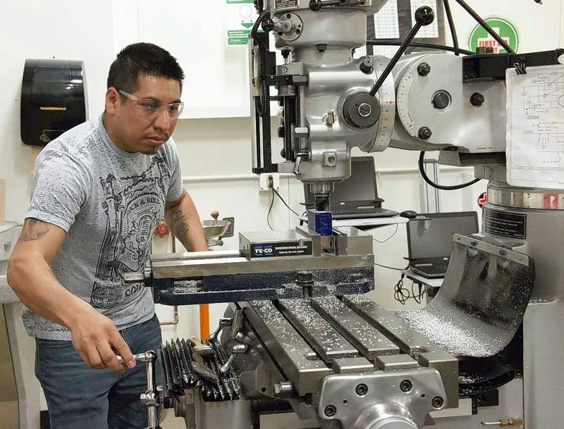 "McHenry County College Industrial Maintenance Technician apprentice Artemio ""Temo"" Martinez of McHenry works on a class project using the Computer Numerically Controlled milling machine. He is one of eight students who joined MCC's new Apprenticeship Program for advanced manufacturing."