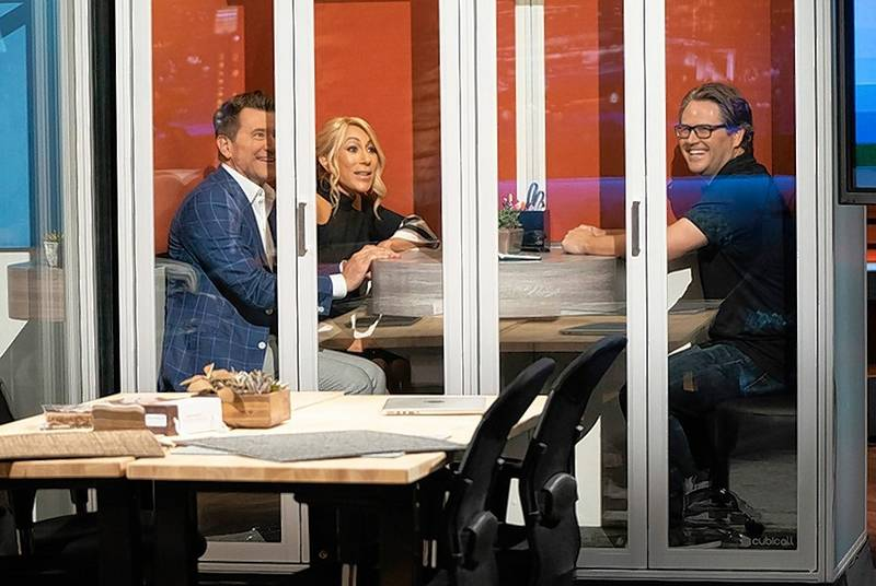 """Shark Tank"" panel members Robert Herjavec, left and Lori Greiner test out a Cubicall portable office phone booth with Cubicall Co-founder Anthony Pucci."