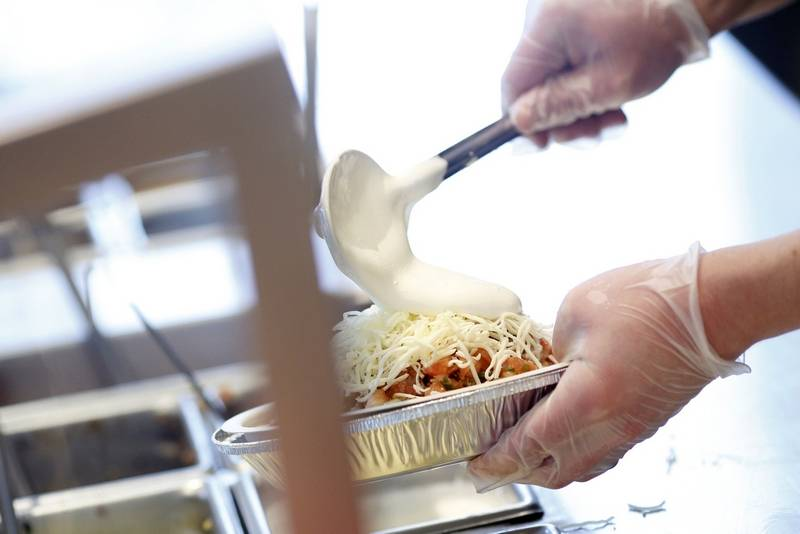 An employee adds sour cream to a burrito bowl at a Chipotle Mexican Grill Inc. restaurant. Chipotle estimates the Mexico tariffs, if enacted, could cost them $15 million this year.