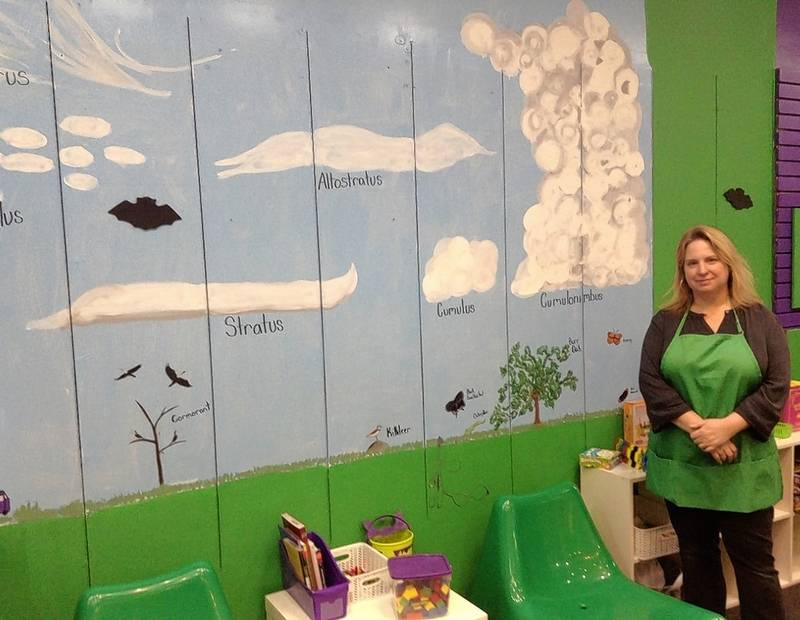 Mary Stupen of Palatine shows the mural of cloud types her daughter helped her with on the wall of her new Purple Me Green, The Science Store location at Woodfield Mall in Schaumburg.