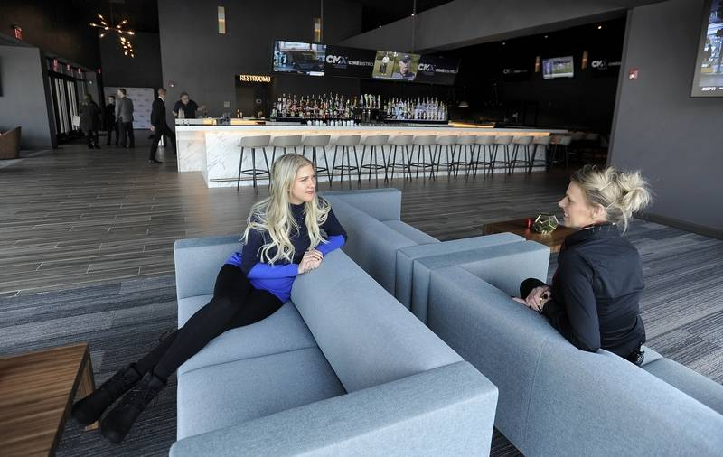 Laura Ginebra, left, and Paula Stanga get comfortable on the sofa in the bar area of the new CMX CinéBistro Wheeling that is set to open Friday in the Wheeling Town Center.