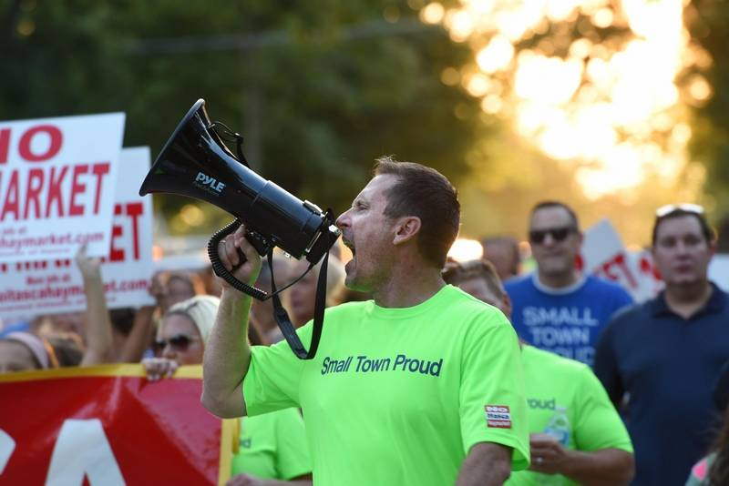 James Diestel uses a bullhorn in September 2019 to lead a large group opposing a proposal to convert a hotel into a drug and alcohol treatment facility in Itasca.